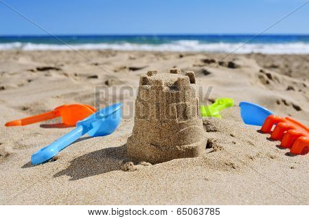 a sandcastle and toy shovels on the sand of a beach