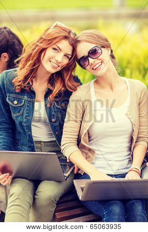 summer holidays, education, campus, technology and teenage concept - two female students with laptop computers