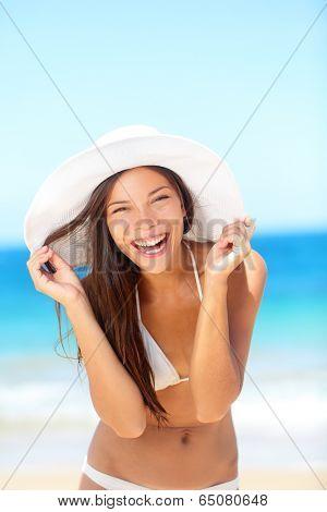 Beach woman happy on travel laughing cute enjoying sun tanning on travel smiling under blue sky. Cheerful beautiful bikini girl having fun on beach. Fresh mixed race Asian Caucasian model on holidays.