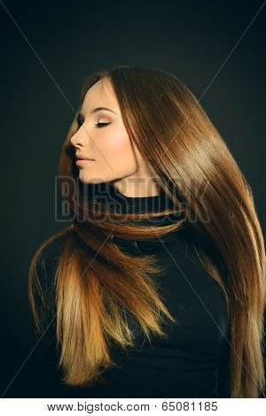 Beautiful girl with magnificent long hair in motion posing over black background.
