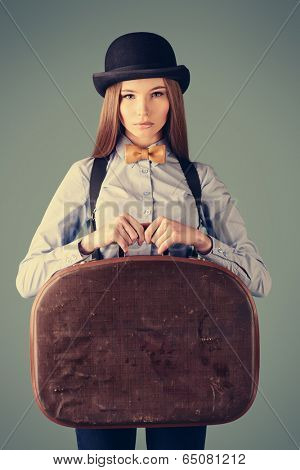 Portrait of the elegant girl model in bowler hat holding her old suitcase. Refined style of old Europe.