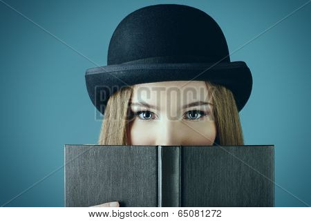 Close-up portrait of the elegant girl model in bowler hat reading a book. Refined style of old Europe.