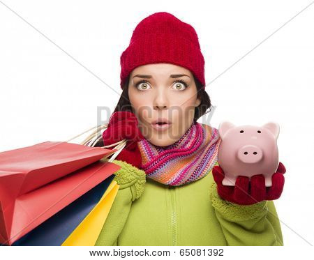 Concerned Mixed Race Woman Wearing Winter Clothes Holding Shopping Bags and Piggy Bank Isolated on White Background.