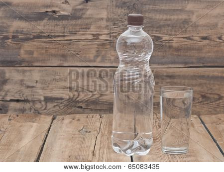 Water bottle with glass on wooden table