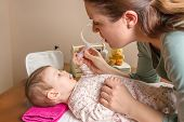 stock photo of nasal catarrh  - Mother cleaning mucus catarrh of adorable baby with a nasal aspirator - JPG
