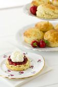 pic of devonshire  - English Cream tea scene with scones Cornish style on china plate with cake stand behind - JPG