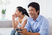 picture of ignore  - Woman being ignored by boyfriend playing video games at home in the living room - JPG