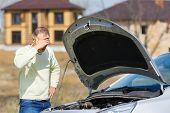 stock photo of irritated  - irritation man in a broken car open hood - JPG