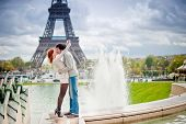picture of enamored  - Lovers kissing in Paris with the Eiffel Tower in the Background - JPG