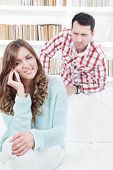 foto of envy  - jealous worried man peering over the shoulder of his girlfriend while she is talking on the phone smiling - JPG