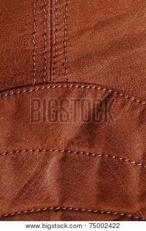 Seams in brown leather jacket. Lower back detail