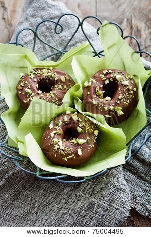 Chocolate donuts with crushed pistachios on top