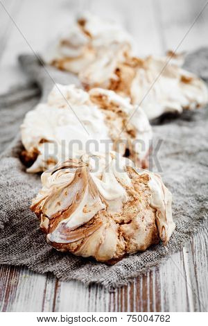 Homemade white meringues with brown chocolate stripes