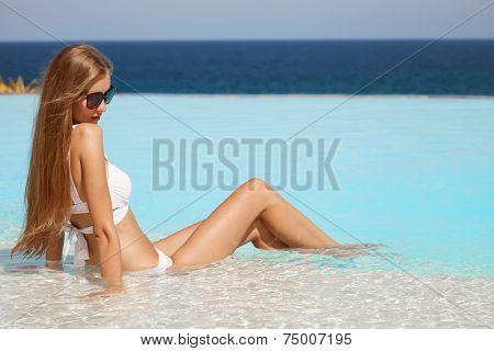 Young beautiful woman sunbathing in swimming pool. Nice sea view.