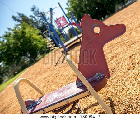 Red Rocking Horse In Summer With Children's Jungle Gym And Park