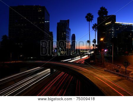 Cars leaving light trails on a downtown Los Angeles freeway at dusk.