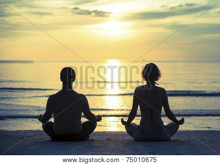 Young couple practicing yoga in the lotus position on the ocean beach during sunset. Cross-process photo style.