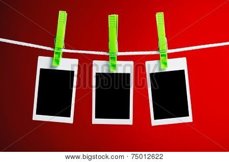 blank photos hanging on rope, red background
