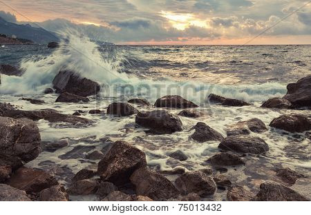 Waves break with splashes about big stones at sunrise