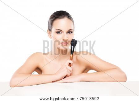 Beauty portrait of young, attractive, fresh, healthy and natural woman with the makeup brush isolated on white