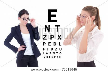 Two Young Attractive Business Women In Eyeglasses And Eye Test Chart Isolated On White