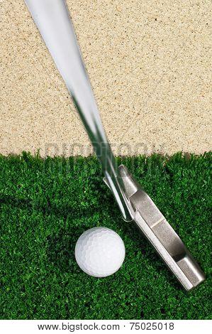 Golf ball and putter on green grass