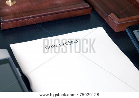 Sheet Of Paper On A Table With The Word New Project. Insert Your Text
