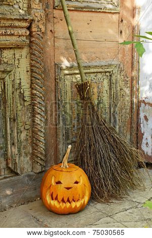 Pumpkin and broom for holiday Halloween on old wooden door background