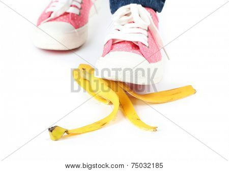 Shoe to slip on banana peel and have an accident, isolated on white