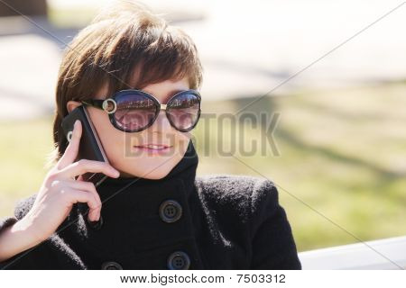 Smiling Woman In Black With Cellphone