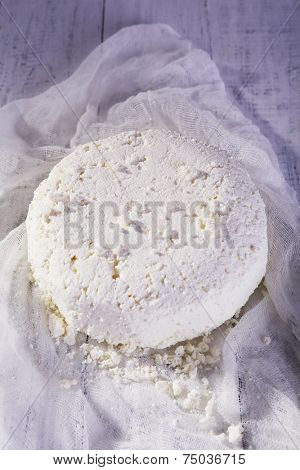 Cottage cheese on gauze on wooden background