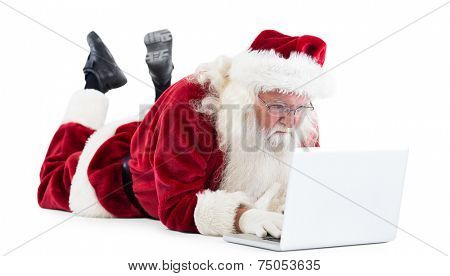 Santa lies in front of his laptop on white background
