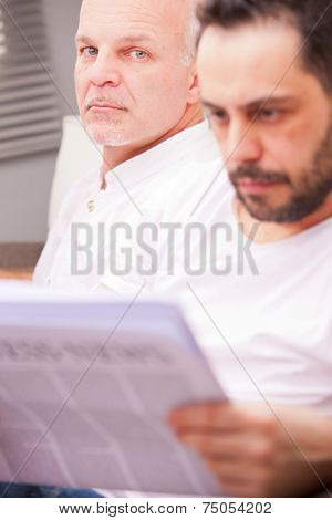 Serious Man With A Friend Reading Newspaper