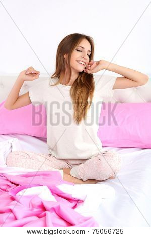 Young beautiful woman awaking while sitting on bed