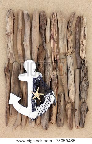 Decorative anchor with abstract driftwood design on beach sand background.