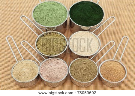 Protein powder health food supplements in metal scoops. Wheat grass, spirulina, hemp, macca root, ginseng, chocolate whey, ginkgo biloba, pomegranate. Top to bottom, left to right.
