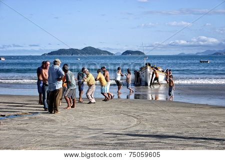 Florianopolis, SC, Brazil - Apr 29, 2007. People helping to pull the fishing boat out of the sea.