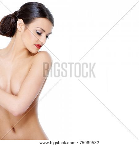 Aesthetic portrait of a nude woman looking over her shoulder into the frame with her arm covering her breasts and downcast eyes  upper body on white with copyspace