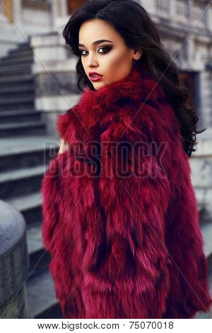 Beautiful Girl With Dark Hair Wearing  Fashion Red Fur Coat