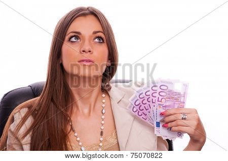 Young business woman sitting in the office chair and holding european bills - isolated on white