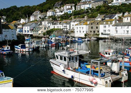 Polperro harbour and village with fishing boats moored waiting for the next tide.
