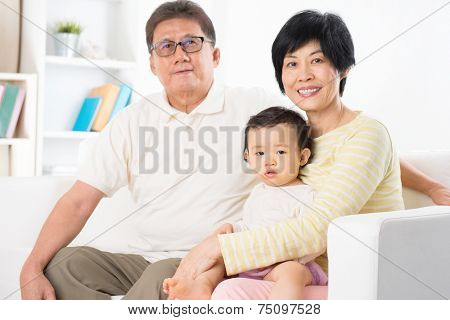 Asian family portrait, relaxing at home, grandparents and grandchild living lifestyle indoor.