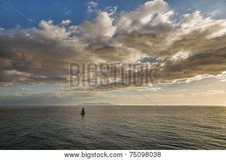 Sailing Boats In Front Of A Silhouetted Island Of Capri