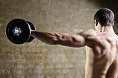 picture of dirty  - Closeup image of man lifting dumbbells in front of dirty wall background t old gym - JPG