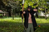 stock photo of longbow  - Beard Man With A Bow And Arrows In The Woods - JPG