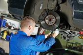stock photo of adjustable-spanner  - car mechanic worker repairing suspension of lifted automobile at auto repair garage shop station - JPG