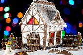 image of gingerbread house  - Decorative snowman and gingerbread house with light inside on blurred lights background - JPG