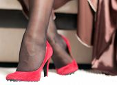 stock photo of stocking-foot  - graceful female legs in red shoes with high heels closeup - JPG
