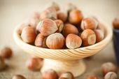 stock photo of hazelnut  - hazelnut in the wooden plate on the table - JPG