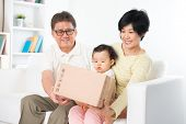 pic of shipping receiving  - Asian family received an express courier parcel and open it at home - JPG